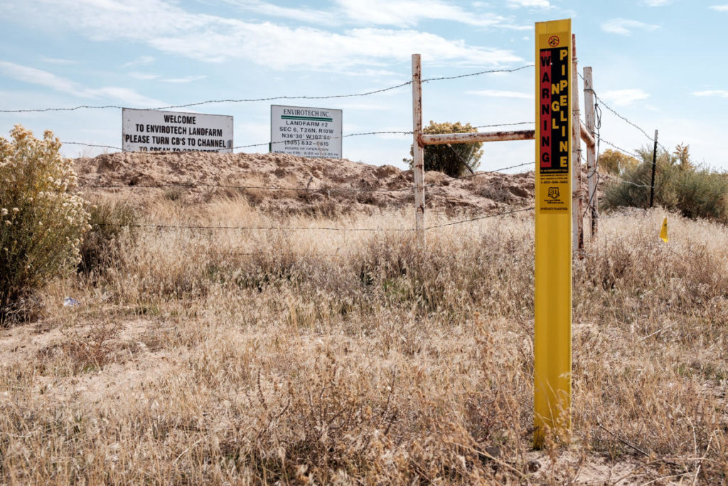 image of oil and gas development and signs in Greater Chaco